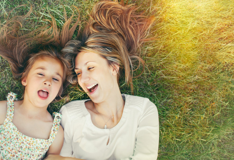 girl and her mother having fun on the grass in sunny